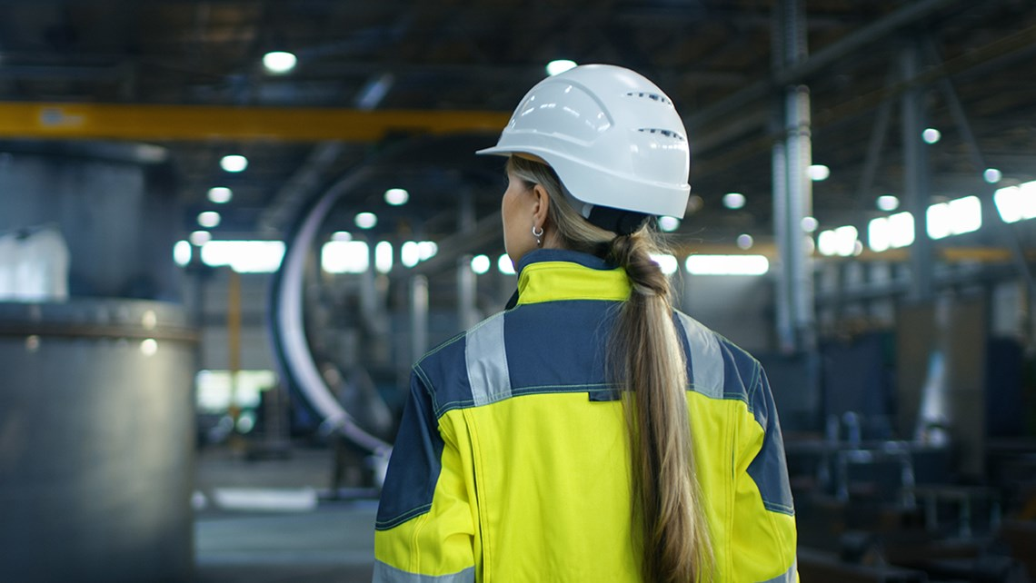 Worker seen from the back in an industrial environment